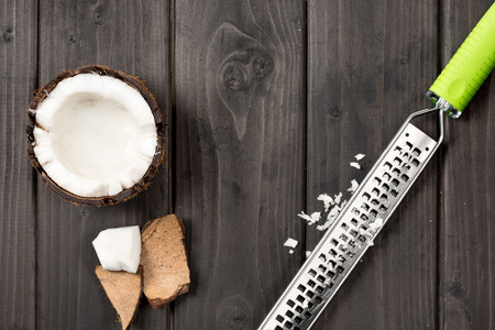 top view of coconut pieces with grater on wooden background, coconut shavings Banco de Imagens
