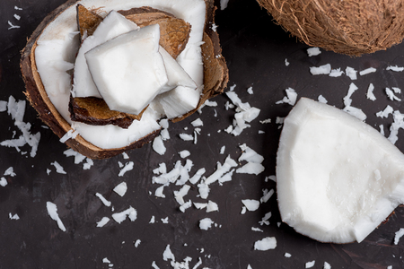 close up of pieces of ripe tropical coconut on dark background, coconut shavings