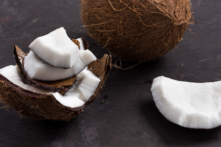 close up of pieces of ripe tropical coconut on dark background