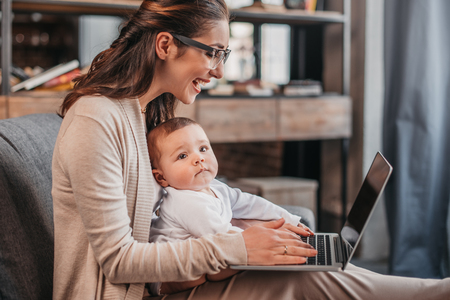 happy mother with her son using laptop at home Stock Photo