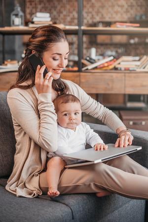 母の笑顔と彼女の息子の世話をしながら自宅で仕事