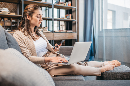 homeoffice: Businesswoman remote working and using digital devices while lying on couch
