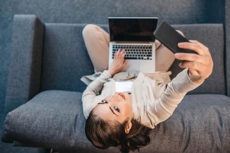 homeoffice: woman in formalwear taking selfie on smartphone during work