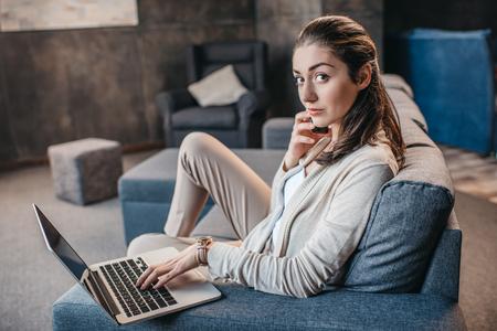 Jonge vrouw die gesprek op smartphone tijdens het werk op laptop hebben thuis