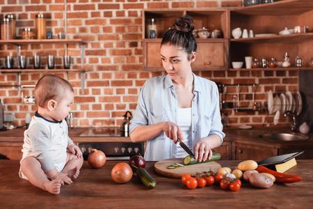 jong gezin samen koken ontbijt. Moeder die komkommer op scherpe raad hakken terwijl haar zoon dichtbij zit Stockfoto