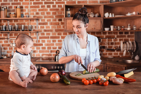 young family cooking breakfast together. Mother chopping cucumber on cutting board while her son sitting near Stock Photo