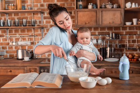 mother holding her son, talking on smartphone and mixing a dough at the kitchen. family life and multitasking concept Foto de archivo