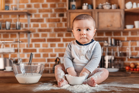 Portrait of little boy playing with flour and sitting on kitchen table