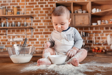 messy clothes: Adorable little boy playing with flour and sitting on kitchen table Stock Photo