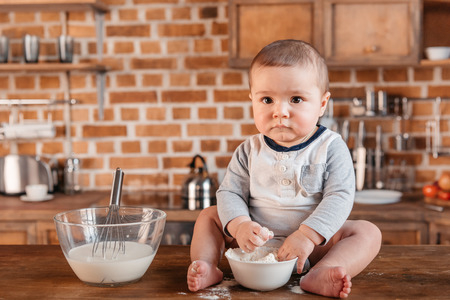 messy clothes: Adorable little boy looking at camera while playing with flour and sitting on kitchen table