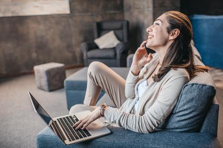 vrouw met gesprek op smartphone tijdens werk op laptop thuis, thuis bedrijfsconcept