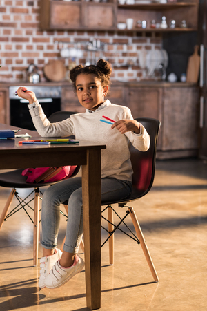 Smiling little girl sitting at table and drawing with felt tip pens Stock Photo