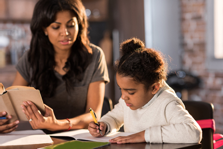 assignments: Mother looking at cute little daughter doing homework at home Stock Photo