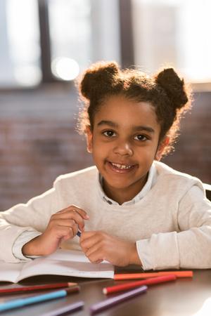Close-up portret van schattige kleine Afro-Amerikaanse meisjestekening met viltstiften Stockfoto