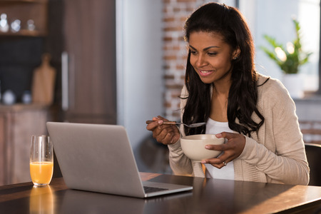 african american woman having breakfast and using laptop at kitchen Stock Photo