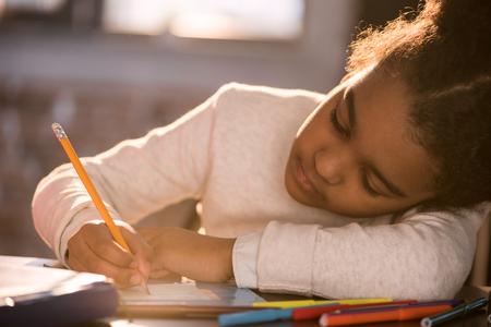 Adorable fille afro-américaine, dessin au crayon, fait des devoirs Banque d'images - 80279363