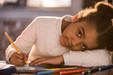 adorable fille afro-américaine, dessin au crayon et regardant la caméra, fait des devoirs