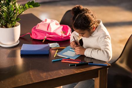 Schattig klein meisje zittend aan tafel en tekenen met kleurrijke viltstiften