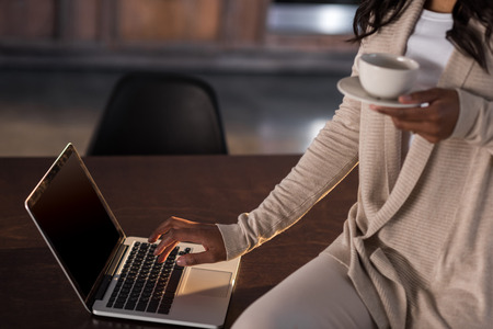 woman drinking coffee and using laptop at kitchen