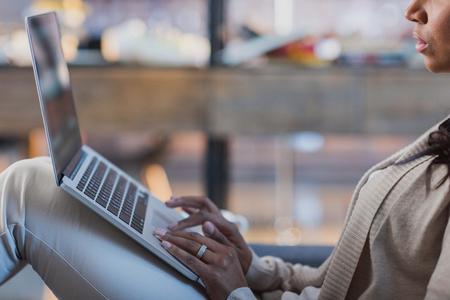 家でノート パソコンを使用してアフリカ系アメリカ人の女性 写真素材