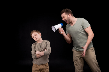 boyhood: Father with megaphone screaming at little son standing with crossed arms