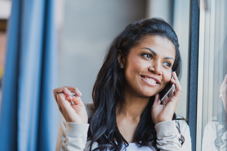 youg african american woman with smartphone near the window at home Stock Photo