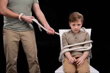boyhood: Cropped shot of father with rope tied little son sitting on chair Stock Photo