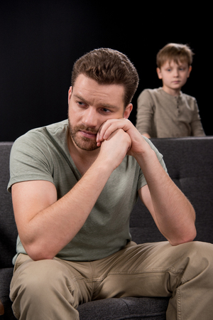 boyhood: Upset little boy looking at pensive father sitting on sofa and looking away