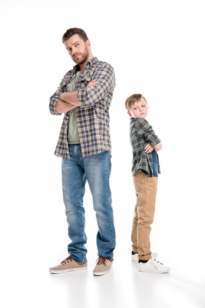 Full length view of serious father and son standing with crossed arms