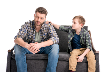Little boy putting hand on shoulder of father sitting on sofa and looking away