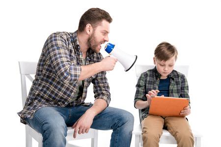 père avec mégaphone criant au fils en utilisant tablette numérique