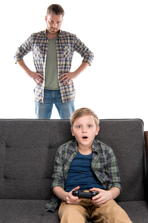 Serious father with hands on waist looking at son sitting on sofa with joystick