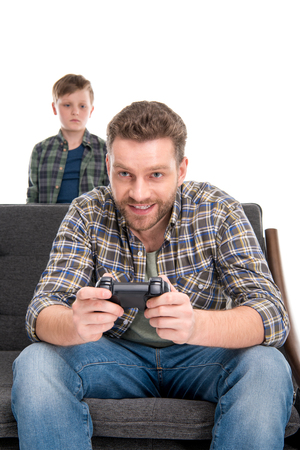 boyhood: Little boy looking at father sitting on sofa and playing with joystick