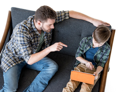 boyhood: High angle view of father sitting on sofa and pointing with finger at son using digital tablet