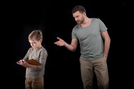 boyhood: Father gesturing and looking at son using digital tablet