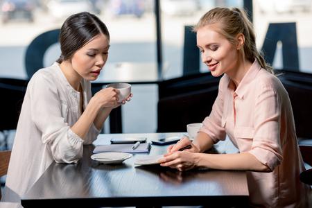若い実業家のノートを見て、コーヒー ブレークでプロジェクトについて議論します。