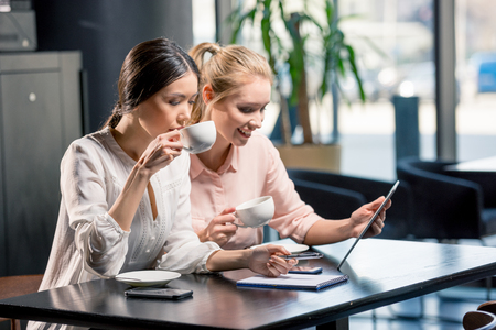 Smiling young women using digital tablet while drinking coffee in cafe