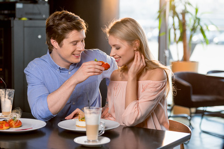 romantic couple in love having lunch together in restaurant