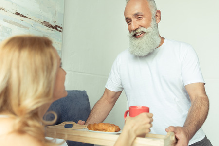 bringing: bearded man bringing tray with breakfast to happy blonde woman in bedroom