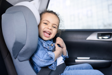 african american girl smiling and sitting in car