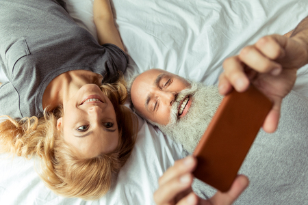 middle aged couple lying in bed and taking selfie