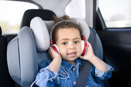 african american girl listening music sitting in car Stock Photo