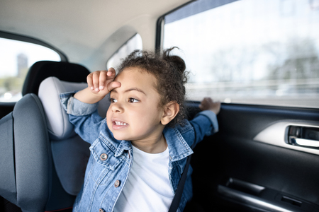 adorable african american girl sitting in car