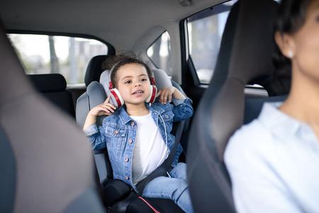 차에서 운전하는 동안 헤드폰에서 음악을 듣고 소녀
