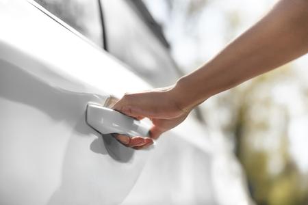 女性が駐車場で車のドアを開く