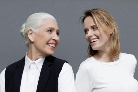 Zwei schöne Frauen, die zusammen stehen und sich lächeln