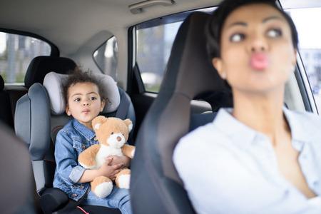 顔をしかめる母と娘一緒に車の運転