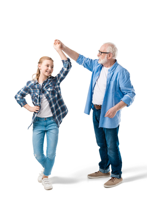 grandchild dancing with grandfather isolated on white in studio