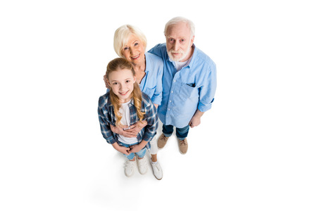 overhead view of happy grandfather, grandmother and grandchild hugging and looking at camera