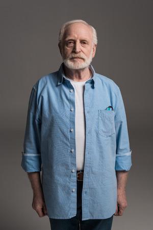 スタジオでの孤立したグレーを立っているひげを生やした男